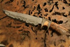 Subhilt made from a tool steel/stainless steel laminate. The handle was carved from maple burl.  The fittings were carved in wax and cast in bronze.
