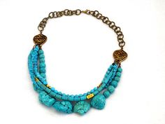 Skye Green, a high impact layered turquoise statement necklace with different sized beads, barrels, chips and nuggets of genuine turquoise gemstone. Handcrafted in our studio as part of our Statement Rock range. Finished off with Indonesian style bronze spacers and an antique bronze effect chain with lobster clasp. The necklace is approximately 18″ (customised sizes available upon request).