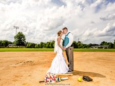 Bride and groom kiss on the pitcher's mound of a baseball field.