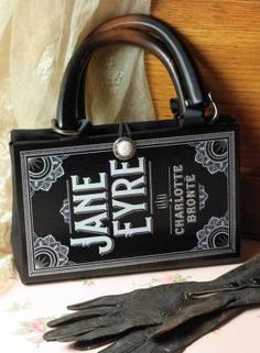 """Jane Eyre Book Purse    A novel idea. An industrious designer converts the Gothic romance into a leather hand bag. Where once there were bound pages, now there is a lined compartment with crochet lace pocket. The spine and back cover excerpt are joined by a faux tortoise handle. Cell phone pocket. 8 x 6""""."""
