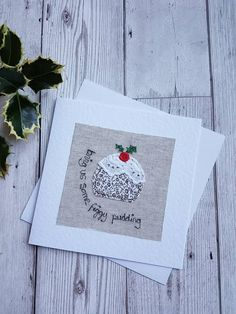 This lovely original textile Christmas greeting card has been designed and made by me. It features a Christmas pudding with the words bring us some figgy pudding. The textile artwork has been produced using appliqué and free motion machine embroidery, and has been attached to a hammered effect white greeting card. The card is blank inside for your own message. The card measures 6 x 6. It comes with a white envelope and is sealed in a clear cello bag to protect it. The picture above is jus...