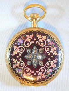 Fine Vacheron and Constantin 18K gold, enamel and diamond ladies antique pendant watch circa 1890. The beautiful case back with dark red enamel (significant surface scratches) with painted flowers and foliage centered with a large diamond flower. Lovely enamel dial with black numerals on blue cartouches separated by fine gold designs and fancy gold hands. Fine 16 jewel nickel movement with counterpoised palled fork and wolf tooth winding.