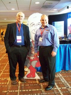 """Bruce Hamilton of GBMP poses with Tony Manos of 5S Supply in front of Bruce's caricature of the """"Old Lean Dude."""""""