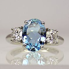 Oval aquamarine with two round brilliant-cut diamonds, one either side, all in claw-collets on platinum shank