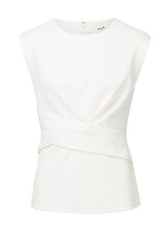 Textured Ponte Wrap Front Peplum Top. Neat fitting sleeveless style features front wrap body with peplum hem in a textured fabrication complete with ponte back body and invisible zipper. Available in Black and Cream as shown.