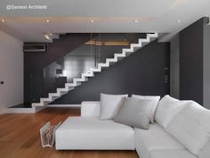 Sala de estar con el impacto estético de la escalera blanca - Arquitectura Sanson Architetti