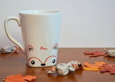 This is a white ceramic mug featuring a cute fox design, with a foxs face on the front and its tail on the back