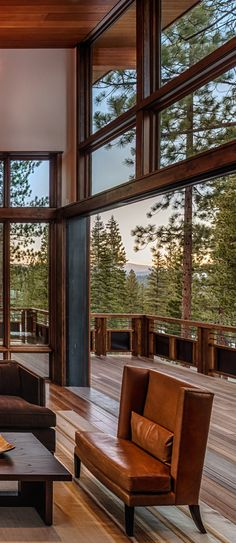 Weiland sliding doors blend a living room area with a large outside deck and a view of the surrounding mountains.