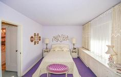 With its bold gemstone purple carpeting, lilac walls, and a fuchsia settee, the master bedroom is like something out of Versailles!