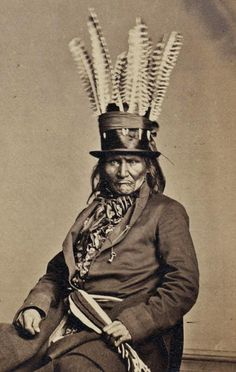A photo of an Anishinaabe man from the western Great Lakes taken in Washington DC in 1862, with his top hat enhanced with the feathers he might have worn in a traditional headdress. The sash around the coat is also very fashionable. Photo is from the Massachusetts Historical Society,
