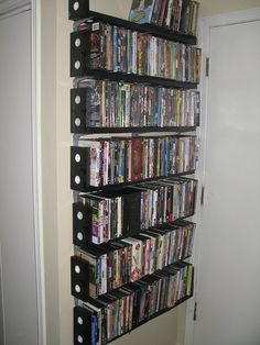 super glue/screw together some old VHS tapes and mount onto L brackets to store DVDs
