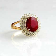 Lady's 14K Yellow Gold Dinner Ring, with an oval 6.25 carat ruby, atop a triple graduated concentric border of round diamonds, on a split sided band, total diam