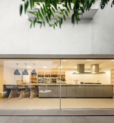 Image 46 of 70 from gallery of Gama Issa / Studio - Marcio Kogan + Lair Reis. Photograph by Fernando Guerra Studio Mk27, Small Sitting Areas, Wood Front Doors, Sliding Doors, Large Kitchen Island, Kitchen Layout, Kitchen Ideas, Indoor Outdoor Living, Interior Design Kitchen