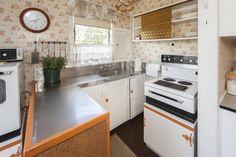 Incredible mixed era kitchen with 60's & 80's features, in 3 bedroom 1960's home @ Pupuke Rd, Birkenhead. (in Dec 2012) Retro split stove (separate hobbs & oven), luvar wood cupboard doors with special orange trim, glass cupboard sliding doors, half window curtain, tiled walls...