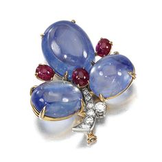 SAPPHIRE, RUBY AND DIAMOND BROOCH, BULGARI, 1960S. Of trefoil design, set with cabochon sapphires and rubies, to the brilliant-cut diamond stem, mounted in yellow and white gold, signed Bulgari.