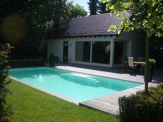 mooi zwembad in de tuin met witte folie en een trap aan de zijkant van het zwembad.