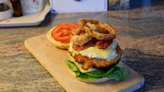 """Make the """"Triple Crisp"""" Burger: onion rings, crunchy bacon and crispy chicken patty balanced by a tartar sauce, some lettuce and tomatoes. Crispy Chicken Burgers, Chicken Patties, Burger Stand, Tartar Sauce, Pickled Onions, Burger Buns, Onion Rings, Salmon Burgers, Lettuce"""