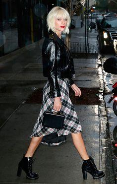 Street style look jaqueta couro preta, vestido xadrez e botas.