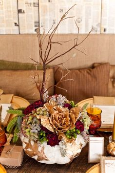 Use a pumpkin painted white, branches, florals, leaves for a Thanksgiving dinner, fall centerpiece