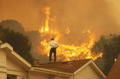 """""""Standing on a rooftop, a man looks at the Springs fire's approaching flames in California Friday May The wildfire, reportedly, 20 percent contained, might be weakened by high humidity and cooler temperatures Saturday May Photo credit: Severe Weather, Extreme Weather, Weather Conditions, California Wildfires, Wild Fire, California Coast, Southern California, Off The Grid, Inevitable"""