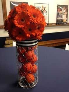 Flower centerpiece: wrap chicken wire around  a cylindrical vase filled with small basketballs, stick orange gerber daisies in a round styrofoam ball and place on top. Voilà! A floral basketball hoop centerpiece.