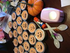 "Decorate applesauce or fruit cups. 2 1/2"" hole punch on orange paper, draw jack-o-lantern on with a sharpie, use glue stick to attach.  Pair with a spoon with a spider ring on it."