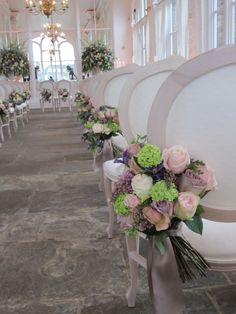 Guide the guest's eye down the aisle with beautiful chair backs, straight to co-ordinating fountains of flowers in large urns.