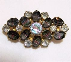 Vintage gray and crystal rhinestone brooch Rhinestones are called Iris because they have embedded rainbow within them. Both inside the main crystal stone and all the dark grey stones Gold Tone setting 1 3/4 x 1 inch Good vintage condition, shows some wear to the back I specialize in vintage rhinestone jewelry, please visit my shop for more selections I do my best to only sell good quality vintage jewelry in good to great condition  International buyers welcome, I now offer 13$ flat rate ...