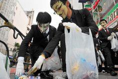 仮面をつけて清掃活動をするアノニマスのメンバーたち