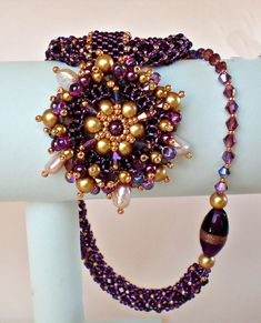 Unique one of a kind beadwoven necklace in beautiful deep colors of purple and gold. The beautiful sparkling colors of exquisite Swarovski crystals
