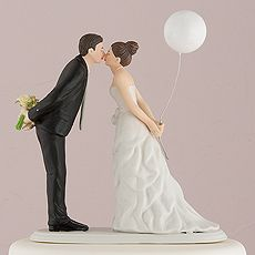 Leaning in for a kiss – balloon wedding cake topper  This couple is sweetly leaning forward for a kiss as husband and wife! Wearing a beautiful bowed dress and clasping a balloon, this beautiful bride is leaning towards her one true love as he holds onto her bouquet.