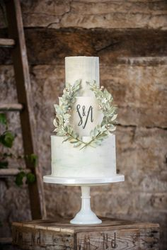 The pale-green marbled cake tiers are decorated with a calligraphed monogram and an elegant laurel wreath made of individually handmade gumpaste leaves and berries that were wired and taped together.