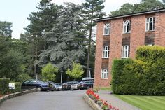 Stanneylands Hotel Manchester- conifers, manicured lawns and pristine flower beds line either side of the long, sloping driveway to this excellent red-brick country house Manchester Hotels, Backyard Fireplace, Airport Hotel, Lawns, Red Bricks, Fenced In Yard, Flower Beds, Pest Control, Lawn And Garden