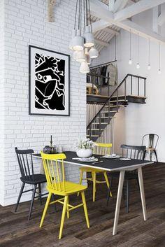 dans le loft de style industriel en noir et blanc loftavec un mur de briques blanches et un escalier de type atelier en bois et métal acier, l'originalité dans la salle à manger est apportée avec un chaise jaune et des chaises dépareillées autour de la table
