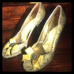 Gorgeous Gold Brocade Jeweled Bow Pumps Heels If you love vintage style looks, he will love the shoes. Beautiful metallic gold and dark gray brocade fabric. Have a satin gold bow on the tow with a metal and rhinestone appliqué. Shoes are a little stiff from being in the closet. Some of the gold lining on the inside of the shoes is starting to crack and break a little. This does not affect wearing the shoes. Have been worn twice BCBGirls Shoes Heels