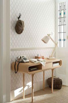 Un petit bureau en bois blond qui s'offre des courbes extravagantes et qui repose devant une tapisserie aux allures géométriques et vintage. Le téléphone en bakélite qui nous offre un bond dans le passé, et cette lampe aux lignes franches qui vient contraster.
