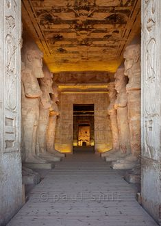 [Egypt 29750] 'Interior of the Great Temple at Abu Simbel.'  Massive statues of Ramses II adorn the pillared hall of the Great Temple at Abu Simbel. At the end we see the sanctuary of the temple. Of the four seated gods residing there we only discern two from this angle: Amun and the deified Ramses. This temple is the greatest of the seven rock-cut temples which Ramses constructed in Nubia in the 13th century BC. It was not seen by Europeans until the 19th century, when it was discovered by…