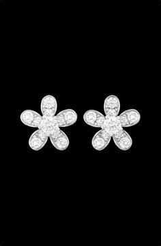 Une paire de puces d'oreilles en or blanc 750/ooo signées de la Maison Van Cleef & Arpels, modèle Socrate formant une fleur sertie de 22 diamants de taille brillant. Système Alpa en o blanc 750/ooo.  Poids totale des diamants: 0,59 carats.  Diamètre: 1 cm.  Prix du neuf: 6 950 euros.