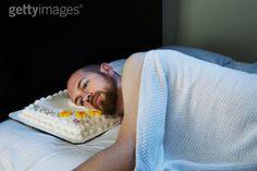 Un homme méditant sur ses erreurs passées tout en utilisant un gâteau comme oreiller :