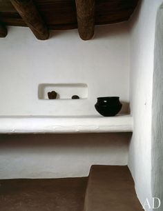 """The Indian Room took its name from the narrow adobe ledges that early Indian inhabitants used as beds. Having faithfully restored the wooden ceiling and adobe walls, O'Keeffe recognized that """"building in adobe is like a disease. Once you start using it, you can't really ever stop."""" A Pueblo Indian pot glows in this context."""
