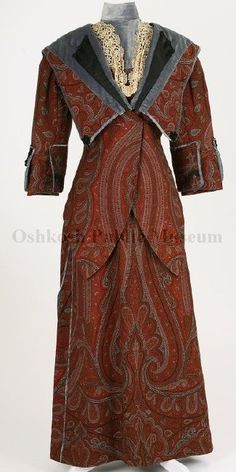 """Dress, ca, 1909 to 1915  ID: I11.5.2.1  """"Paisley pattern fabric in red rust, blue and green; accented with light blue velvet trimmed with black silk, off-shoulder collar, edged with light blue velvet extends down front of jacket, three frog-buttons decorate left and right side of collar which extends to bodice back forming a V from which a black velvet tassel is attached. Set in sleeves extend to wrists."""""""