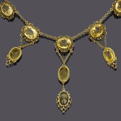A late 19th century citrine and gold pendant necklace, circa 1890  The trace-link chain set to the centre with five oval mixed-cut citrines within gold scroll borders suspending three citrine swing drops with chain-link connections, length 40.5cm., fitted case