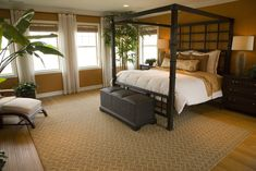 This master bedroom features a bamboo style four poster bed, black wicker ottoman, and a modern adirondack chair seated in the corner.