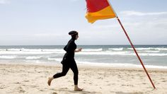 "Twenty-year-old trainee volunteer surf life saver Mecca Laalaa runs along North Cronulla Beach in Sydney during her Bronze medallion competency test January 13, 2007. Specifically designed for Muslim women, Laalaa's body-covering swimming costume has been named the ""burkini"" by its Sydney based designer Aheda Zanetti.   REUTERS/Tim Wimborne (AUSTRALIA) - RTR1L4WG"