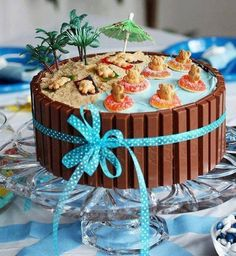 Easy Cake Decor. Cover round cake with chocolate frosting, assemble Kit Kat's around the edges, use blue icing for the water and brown sugar for the sand, use candies such as Teddy Graham's and gummy rings for decoration