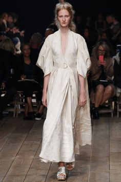 This item is from the See the Alexander McQueen Spring 2016 Ready-to-Wear collection. This garment is inspired by the trench coat which was very popular during WW2. During and after the war the designers tried to make the trench coat into a luxury item, much like this garment. The color and the shape are the aspects that are most similar to a traditional trench coat.