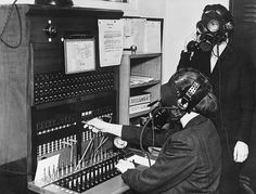 London, England 1939. Telephone operators at Westminster Hospital wearing special gas masks with microphone attachements so that they can continue to work during German Luftwaffe air raids.