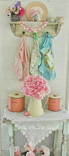 This whole photo is lovely - from the lace on the table the pitcher of flowers - the old canisters - the old aprons like my grandma used to wear - and the cute rack they are hanging on