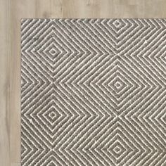 Lend a touch of charm to your living room or define space in the entryway with this lovely wool rug, featuring a classic flat woven diamond design in gray and white.