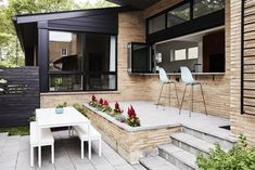 In the front courtyard, a raised bluestone patio was built off the new kitchen for casual meals and entertaining. The Eames Molded Plastic Chairs are from Herman Miller. The dining table and benches are from Room & Board. Tagged: Outdoor, Shrubs, Wood Fences, Wall, Gardens, Horizontal Fences, Wall, Stone Patio, Porch, Deck, and Front Yard. Photo 5 of 15 in Midcentury Mashup: A 1950s Ranch House in Chicago Gets a Palm Springs-Style Butterfly Roof #roofgardens #frontgardenshrubs #wallgardens